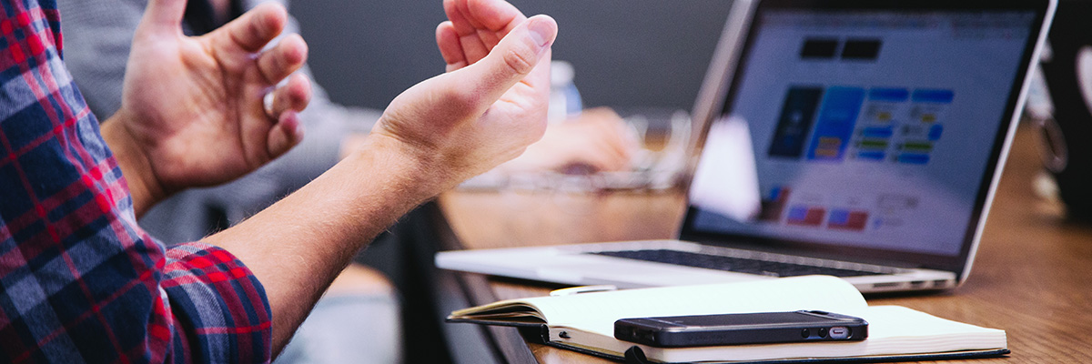 A picture of gesturing hands in front of an open notebook and a laptop.